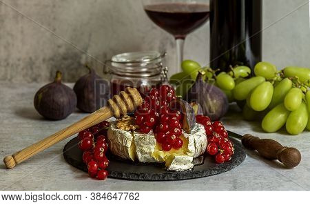 Mouthwatering Oven Baked Camembert With Walnuts, Honey, Figs, And Red Currant. Branch Of Green Grape