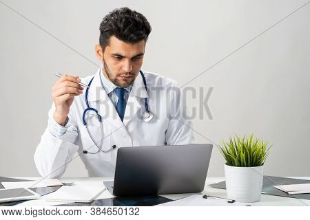 Serious Arab Practitioner Working At Computer. Handsome Physician In White Medical Gown With Stethos