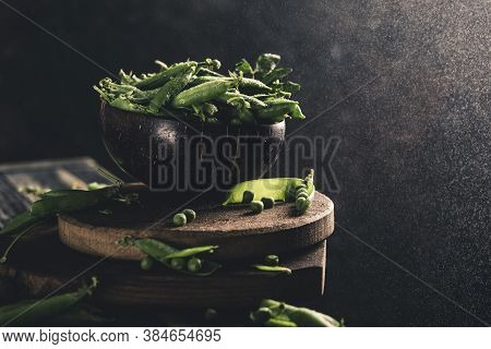 Green Pea Pods In A Coconut Bowl With Dew Drops On Wooden Planks On A Dark Background With Splashes