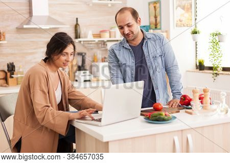 Wife Searching Salad Recipe On Laptop In Kitchen Together With Husband. Man Helping Woman To Prepare
