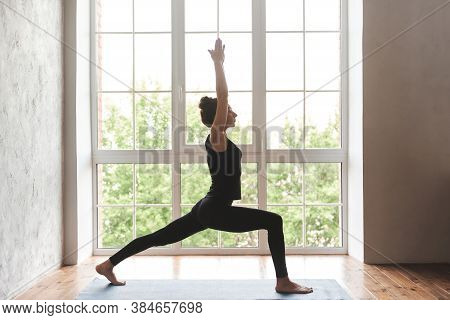 Middle Aged Woman Practicing Yoga, Standing In Warrior One Exercise, Virabhadrasana I Pose, Wearing