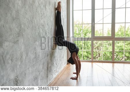 Yogi Mid Aged Woman Practicing Yoga, Standing In Downward Facing Tree Pose, In Sportswear, Doing Adh
