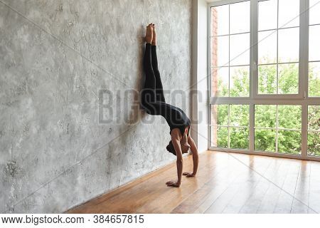 Woman Practicing Yoga, Standing In Downward Facing Tree Pose, In Sportswear, Doing Adho Mukha Vrksas