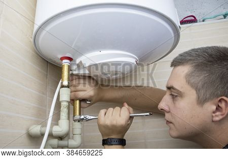 The Boiler Repair Technician Uses An Adjustable Wrench To Unscrew Or Tighten The Nut On The Pipe. In