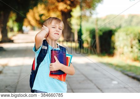 Unhappy School Boy With Book In Hands And Backpack. Upset Kid Going To School. School Bullying, Depr