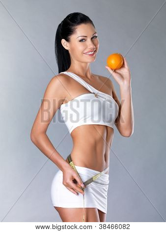 Smiling Girl Measures Figure With A Measuring Tape And Holding Orange