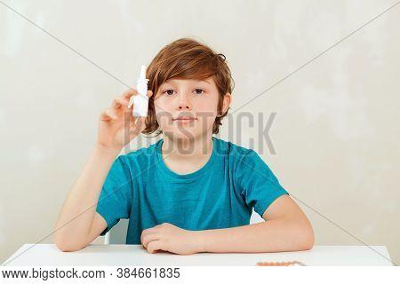 Sick School Boy With Runny Nose Using Nasal Medicine Spray. Nasal Allergy. Kid With Ill Disease Trea