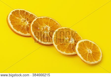 Dehydrated Slices Of Dried Oranges Diagonally Against A Bright Yellow Background. Healthy Food Conce