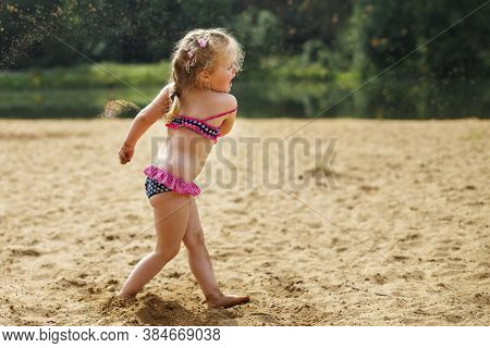 Girl Throws Sand. Beautiful Girl Playing With Sand On Beach. Child Having Fun. Vacation Happiness An