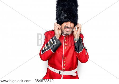 Middle age handsome wales guard man wearing traditional uniform over white background covering ears with fingers with annoyed expression for the noise of loud music. Deaf concept.