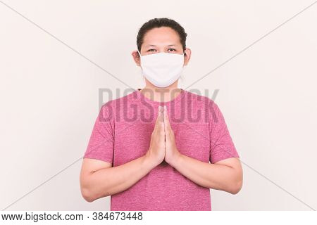 Portrait Of Asian Man Wearing White Fabric Mask And Showing Thai Greeting (wai Gesture)