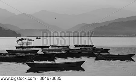View Over A Few Wooden Boats On Phewa Lake In Pokhara, Nepal With The Surrounding Mountains In The B