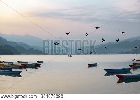 View Over A Few Colorful Boats On Phewa Lake In Pokhara, Nepal With The Surrounding Mountains In The