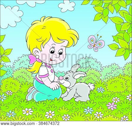 Smiling Little Girl Playing With Her Small Grey Bunny Among Flowers On Green Grass On A Summer Day,