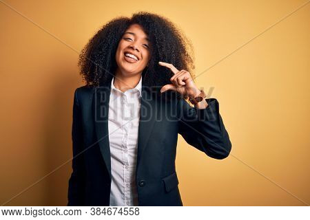 Young beautiful african american business woman with afro hair wearing elegant jacket smiling and confident gesturing with hand doing small size sign with fingers looking and the camera. Measure