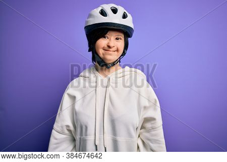 Young down syndrome cyclist woman wearing security bike helmet over purple background with a happy and cool smile on face. Lucky person.
