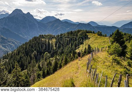 Young Woman Summer Hiker With Backpack Climbingsteep Slopes, Panoramic Peaks Andmountains Withval