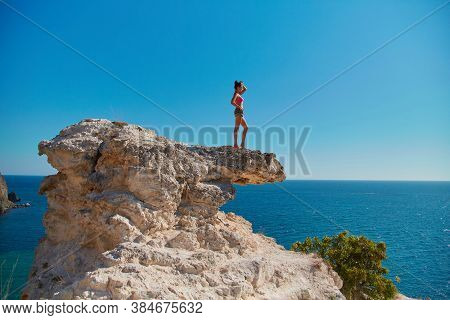 Holiday Time. Summer Adventure. Beach Vacation. Woman Standing On Sharp Cliff. Breathtaking Seascape