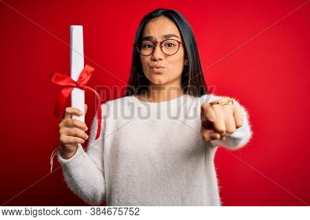 Young beautiful graduate asian woman holding university degree diploma over red background pointing with finger to the camera and to you, hand sign, positive and confident gesture from the front