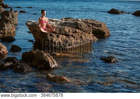 Calm Lady In Pink Bikini Meditating On Rock. Calm Sea. Alone Time. Meditation And Self-absorbed. Spa