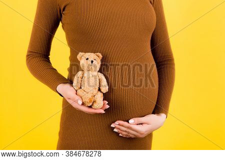 Cropped Image Of Teddy Bear In Hand Against Pregnant Womans Belly In Brown Dress At Yellow Backgroun