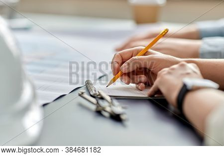construction business, architecture and buiding concept - close up of architect with blueprint, notebook and pencil working at office
