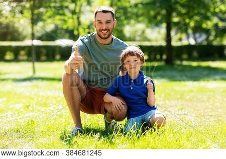 family, fatherhood and people concept - happy smiling father showing thumbs up with little son at summer park