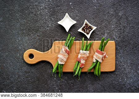 Prepared To Bake Appetizer, Bundle Of Green Beans Wrapped In Bacon On A Wooden Board On A Dark Concr