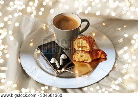 morning, hygge and breakfast concept - smartphone, wireless earphones, cup of coffee and croissants with garland lights on plate in bed at home