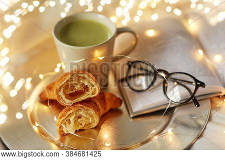 hygge and breakfast concept - croissants, cup of matcha tea book and glasses in bed at home