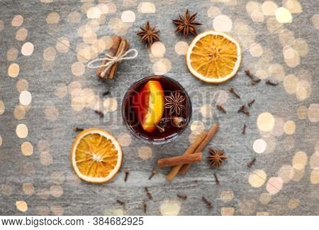 christmas and seasonal drinks concept - hot mulled wine, dry orange slices, raisins with cashew nuts and aromatic spices on grey background