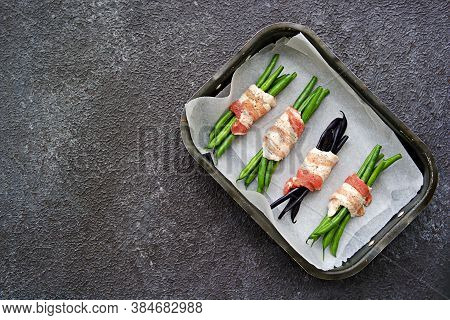 A Baked Appetizer, A Bundle Of Green Beans Wrapped In Bacon In A Metal Baking Dish Against A Dark Co