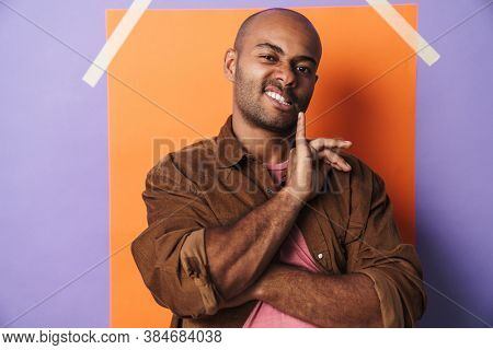 Image of cocky african american guy grimacing and pointing finger upward isolated over multicolored background