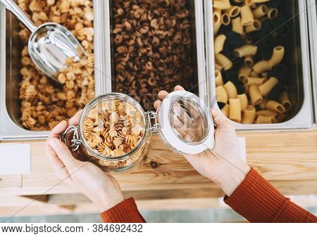 Close-up Of Glass Jar With Pasta In Zero Waste Shop. Woman Buying Bulk Foods In Plastic Free Grocery