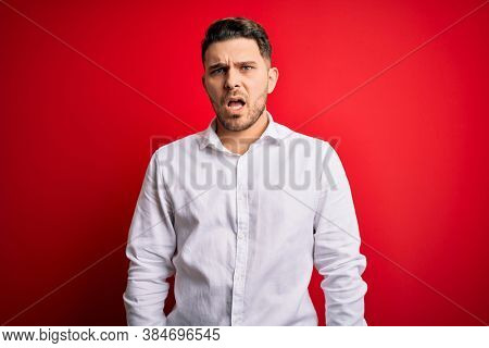 Young business man with blue eyes wearing elegant shirt standing over red isolated background In shock face, looking skeptical and sarcastic, surprised with open mouth