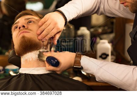 Cropped Close Up Of A Handsome Young Bearded Man Having His Beard Shaved At The Barbershop Professio