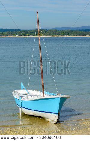 Wooden Blue Fishing Sailboat Anchored Near The Shore