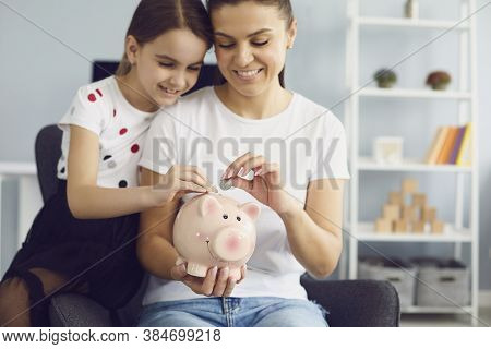 Happy Young Mother And Her Lovely Daughter Putting Coins Into Piggybank Together At Home, Copy Space