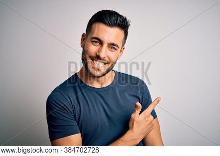 Young handsome man wearing casual t-shirt standing over isolated white background cheerful with a smile of face pointing with hand and finger up to the side with happy and natural expression on face