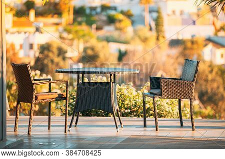 Wicker Furniture - Table And Chairs In A Wooden Terrace.
