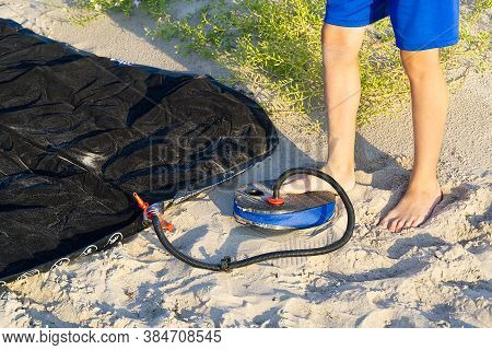 A Man With Air Foot Pump Pumps An Inflatable Mattress Or Air Bed At Sandy Beach. Foot Inflates Air M