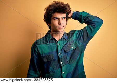 Young handsome man wearing casual shirt standing over isolated yellow background confuse and wondering about question. Uncertain with doubt, thinking with hand on head. Pensive concept.
