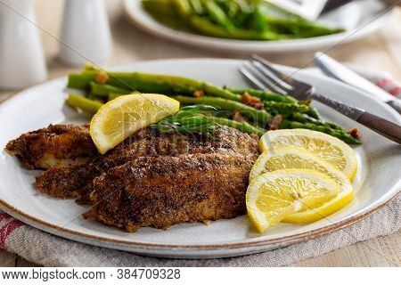Baked Tilapia Fish Fillets With Sliced Lemons And Asparagus On A Dinner Plate