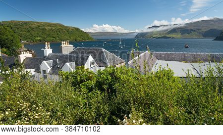 View Of Sea Bay And House Roofs In Portree, Isle Of Skye, Scotland  On Sunny Summer Day. The Largest