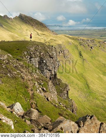 Adult Man Looking At The Storr And Valley - Rock Formations In Trotternish Landslip, Isle Of Skye, S