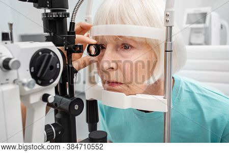 Senior Woman Eyesight Test With Binocular Slit-lamp. Checking Retina Of A Female Eye Close-up. Visio