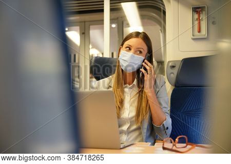 Businesswoman commuting by train, working on laptop and wearing face mask