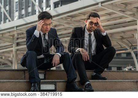 Asian Business Man Sitting On A Staircase Between A Tall Building, Stressed And Fear By A Business P