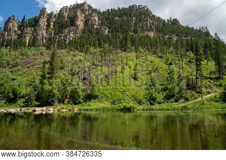 Spearfish Canyon At The Old Dam With Reflection Of The Mountains In The Calm Waters Of The Creek