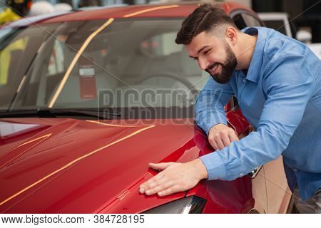 Happy Handsome Bearded Man Smiling, Examining Beautiful Red Automobile On Sale At Car Dealership, Co